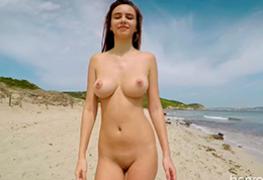 Alisa andando na praia de nudismo de Ibiza
